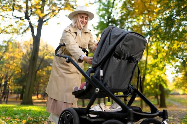 秋の公園を歩いているベビーカーを持つ母