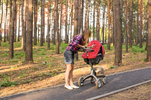 Mother with baby in pram walking in summer park
