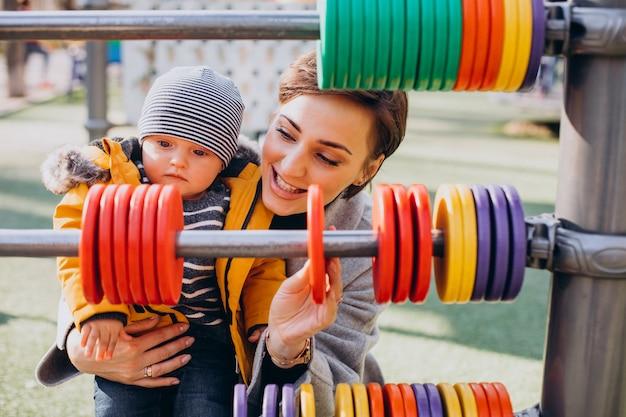 遊び場で楽しんでいる赤ん坊の息子を持つ母
