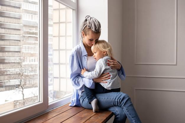 창이에 앉아 놀고 아기 아들과 어머니