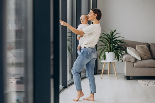 Madre con figlio bambino in piedi a casa vicino alla finestra