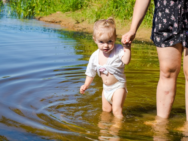 호수에서 물에 튀는 아기와 어머니