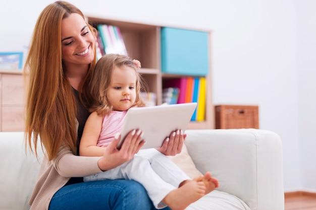 自宅でデジタルタブレットを使用して赤ちゃんを持つ母親