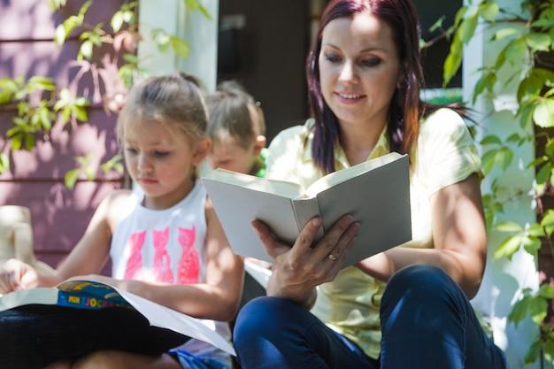 子供と一緒に座っている本を持つ母