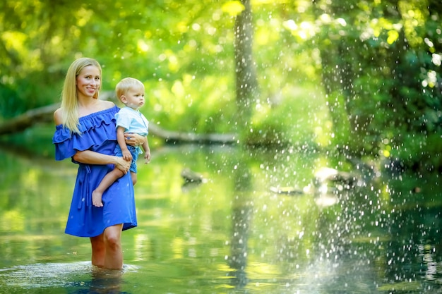 Mother with child 3 year on the hands of enjoyment in the forest river