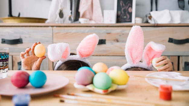 Mother with child in bunny ears hiding behind table with colored eggs
