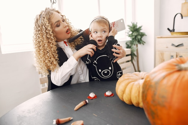 Mother with child in costumes and makeup. family prepare to celebration of halloween.
