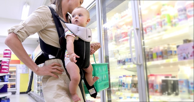 Mother with child in ergo backpack chooses dairy products from refrigerator in store