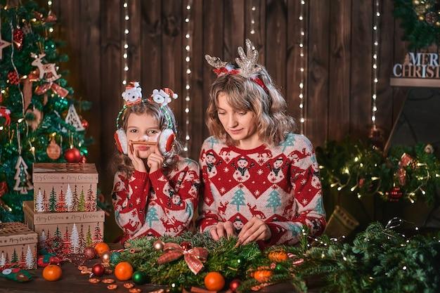 クリスマスツリーの近くの子供の女の子の母。