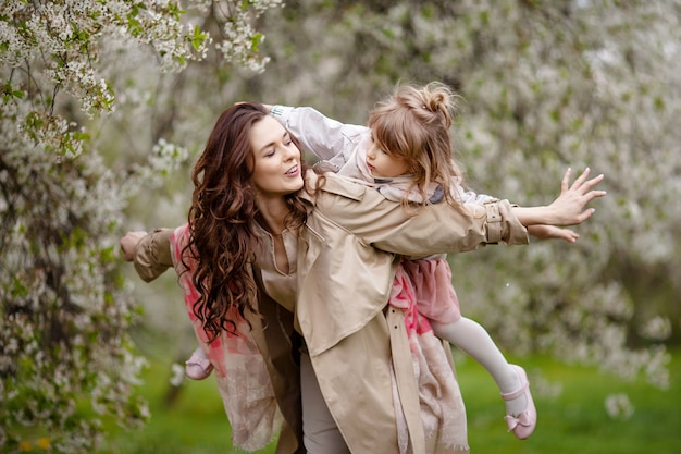 Mother with child girl playing in blooming spring garden. woman with daughter huging and having fun outdoors. concept of happy family