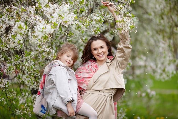 Мать с ребенком девочка играет в цветущем весеннем саду. женщина с дочерью обниматься и веселиться на открытом воздухе. концепция счастливой семьи