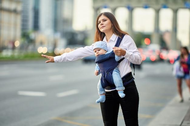 Мать с ребенком в слинге останавливает такси на улице