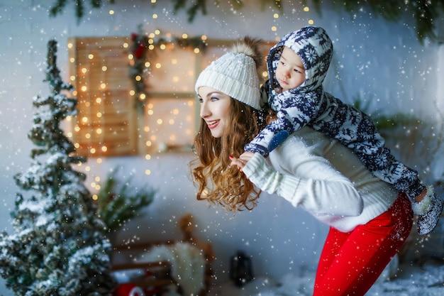 Мать с ребенком на фоне декорации новогоднего дома. люди, одетые в зимнюю одежду