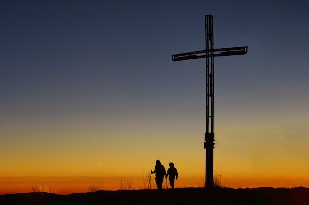 十字架近くの山の頂上に子供を持つ母