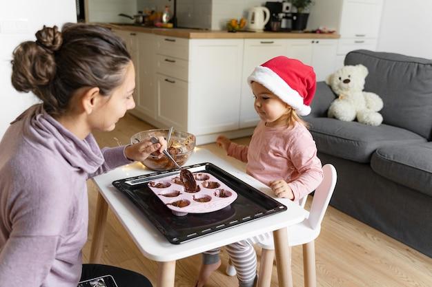 家で休日のクッキーを準備する子供を持つ母。一緒に幸せな家族の時間