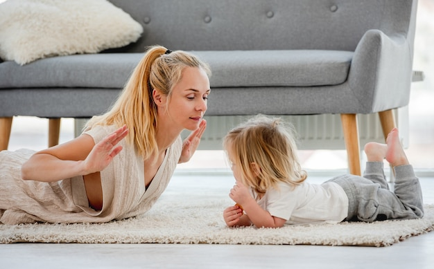 Мать с сыном ребенка вместе делать упражнения, лежа на полу дома