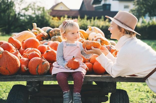 Мать с детьми выбирают тыкву на фермерском рынке happy family autumn concept