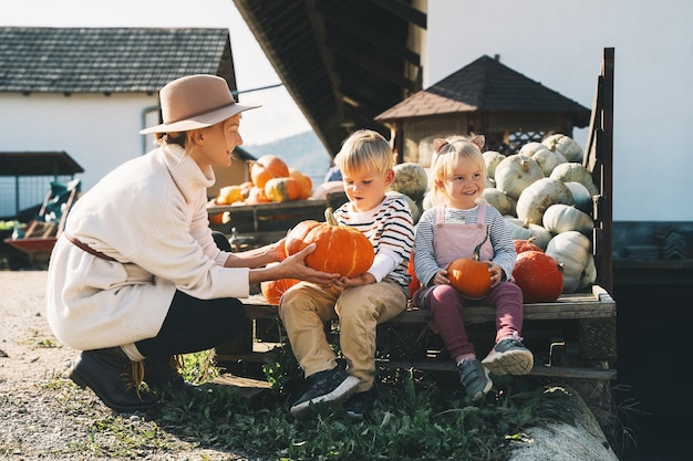 Мать с детьми выбирают тыкву на фермерском рынке, праздничный сезон дня благодарения и хэллоуин