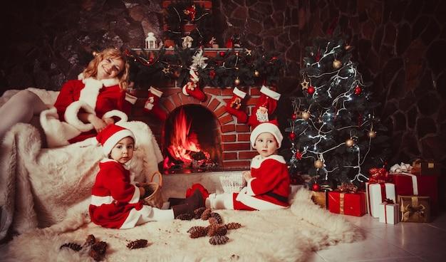 子供を持つ母親は暖炉の近くに座ってコーンで遊んでいます-クリスマスの飾り