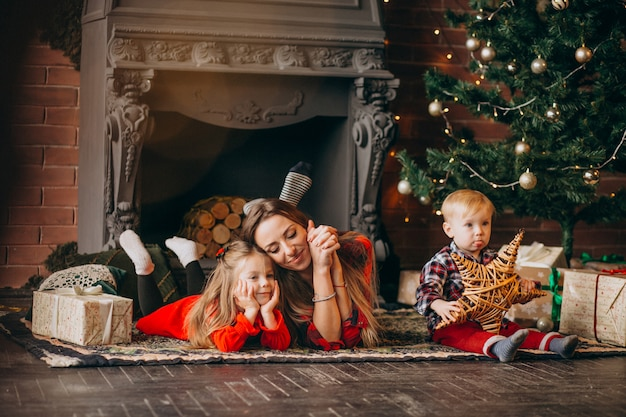 Mother with children by christmas tree