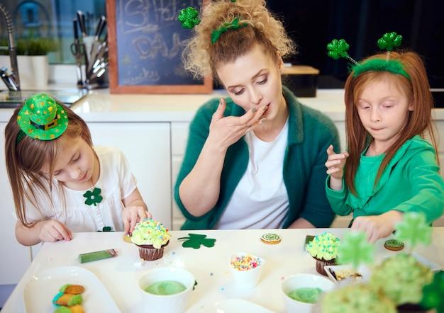 キッチンでカップケーキを飾る子供を持つ母