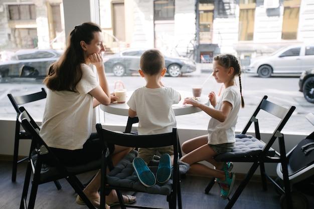 地元のコーヒーショップでホットチョコレートとラテを飲む子供を持つ母親。彼らは笑顔で楽しんでいます。母性の概念