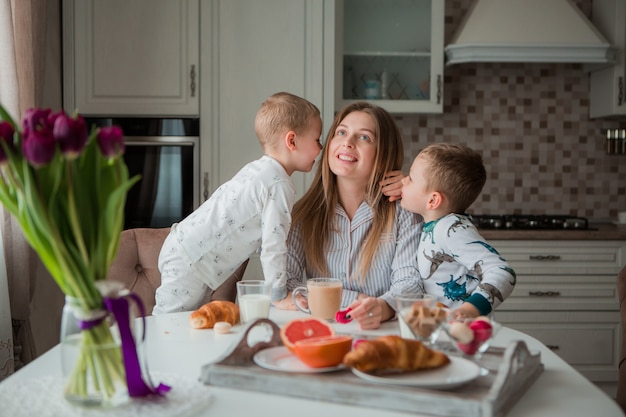 Mother with children having breakfast in the kitchen