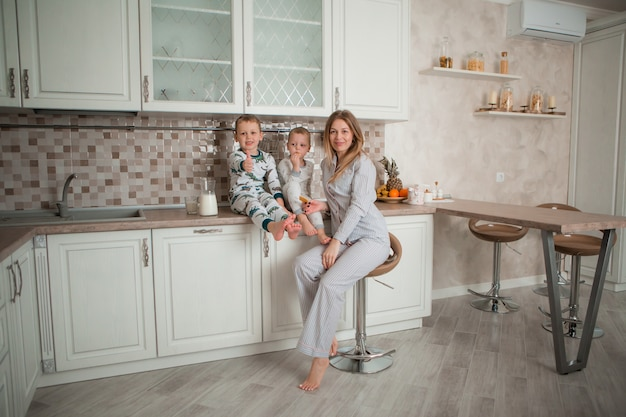 Mother with children having breakfast in the kitchen