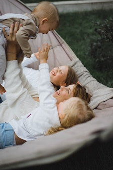 Mother with children having fun in a hammock. mom and kids in a hammock.