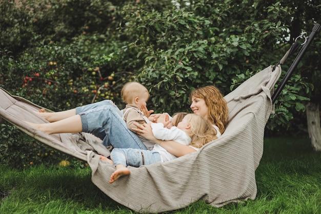 Мама с детьми веселится в гамаке. мама и дети в гамаке.