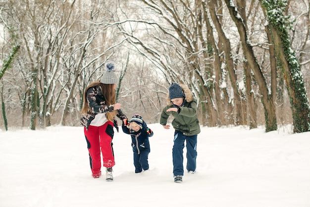 겨울 공원에서 산책을 즐기는 아이들과 어머니. 눈 덮인 겨울 날씨입니다. 즐거운 크리스마스 휴일 보내세요. 가족 겨울 방학. 야외에서 눈을 가지고 노는 행복한 가족. 행복한 어린 시절.