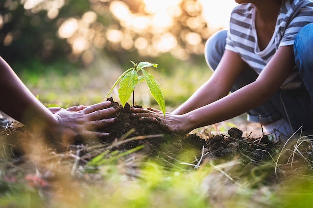 地球を救うために自然の中で植樹を手伝っている子供を持つ母親。環境エココンセプト