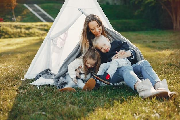 Мать с детьми играет в летнем парке