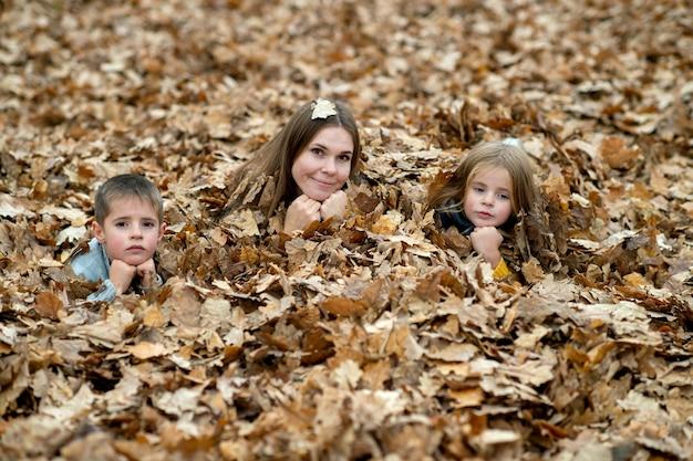葉でポーズをとる子供を持つ母