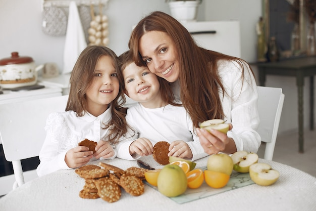 Mother with children sitting in a kitchen and have a meal