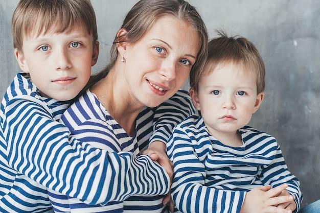子供と息子の幸せなスタジオの肖像画の完全な長さを持つ母
