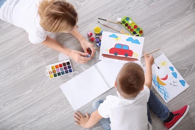 Мать с милым мальчиком рисует картину на листе бумаги, в помещении