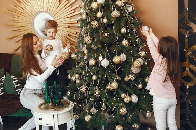 Mother with cute children near christmas tree