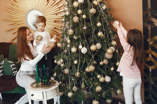 クリスマスツリーの近くのかわいい子供を持つ母