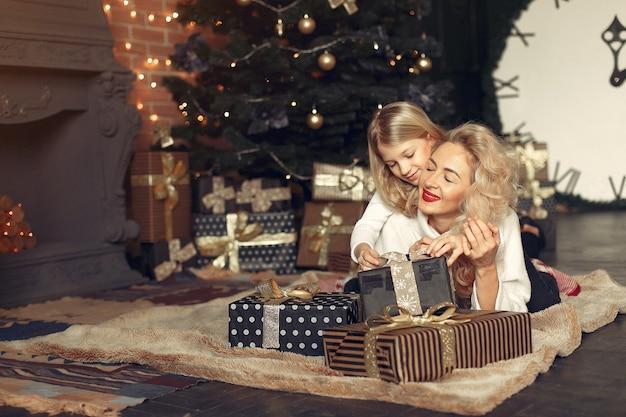 Мать с милой дочерью дома возле елки