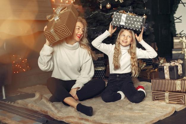 クリスマスツリーの近くに家でかわいい娘と母