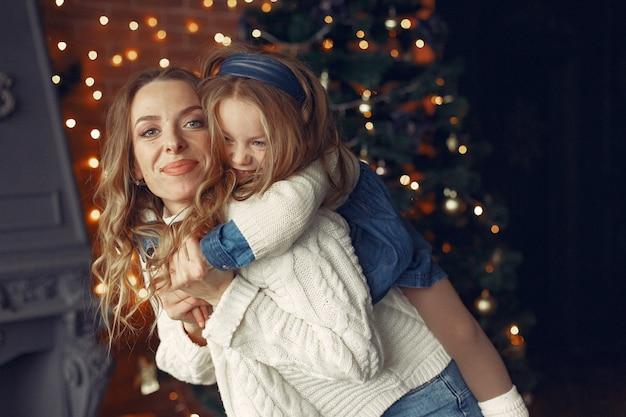 벽난로 근처 집에서 귀여운 딸과 어머니
