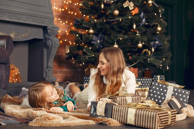 暖炉のそばの家でかわいい娘と母