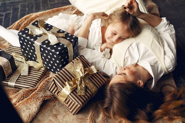 Мать с милой дочерью дома у камина