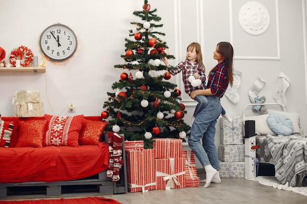 Мать с милой дочерью дома с рождественскими подарками