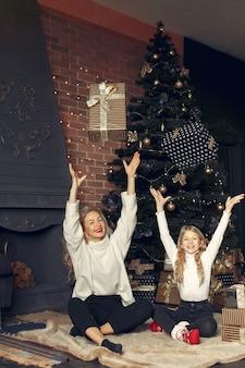 Madre con figlia carina a casa vicino all'albero di natale