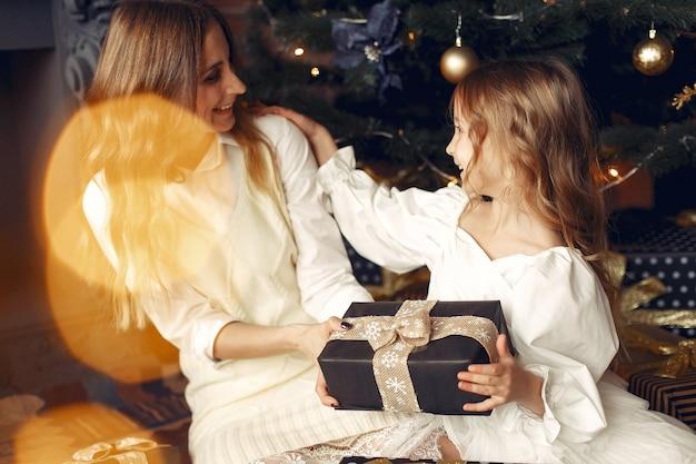 Madre con figlia carina a casa vicino al camino
