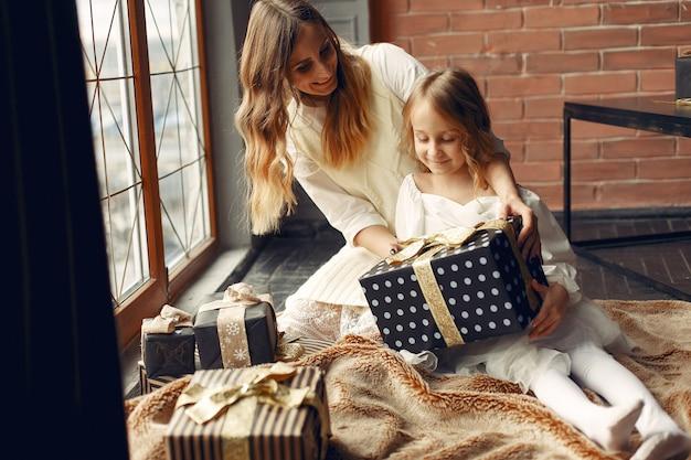 Madre con figlia carina a casa vicino alla finestra