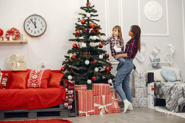 Mother with cute daughter at home with christmas gifts