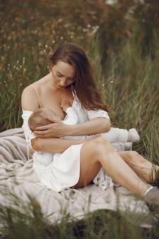 かわいい娘を持つ母。彼女の小さな娘を母乳で育てるお母さん。白いドレスを着た女性。